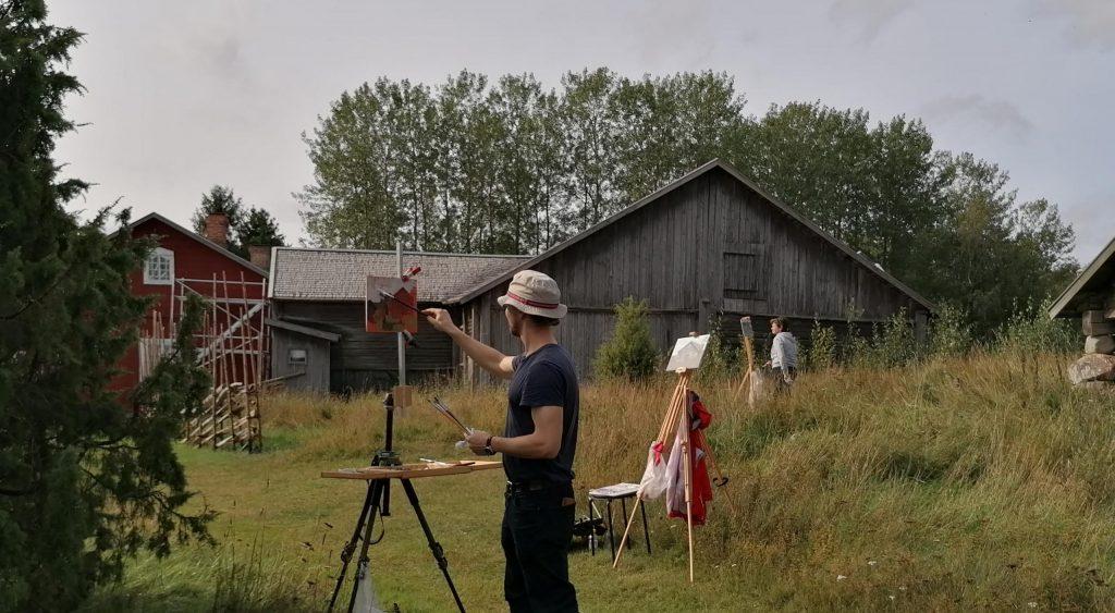 taiteilija maalaamassa ulkona